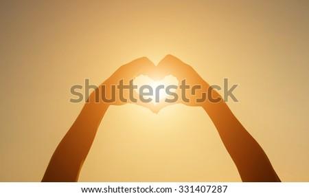 Silhouette hand heart shape with sun light - stock photo