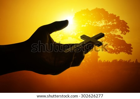 Silhouette Hand holding cross  - stock photo