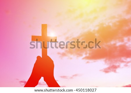 Silhouette hand holding jesus and cross at sunset - stock photo