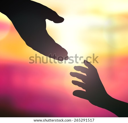 Silhouette hand of a man reaching to hand of GOD over blurred the cross on sunset background. - stock photo