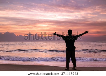 silhouette happiness man on the sunrise beach - stock photo