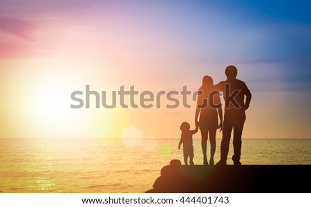Silhouette happy family together, father, mother with little boy or child stay nearly beach or sea during sunset. happy family at beach sunset having happy feeling. Vignette effect concept. - stock photo
