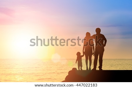 Silhouette happy family together, father, mother with little boy or child stay nearly beach or sea during sunset. happy family at beach sunset. father, mother and boy children having happy feeling. - stock photo