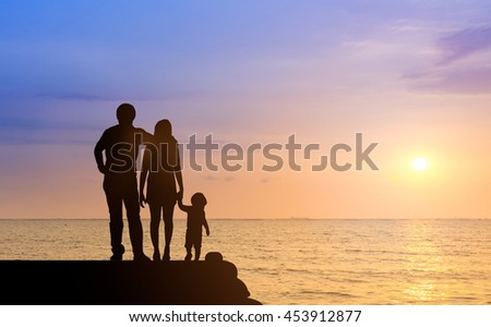 Silhouette happy family together, father, mother with little boy or child stay nearly beach or sea during sunset. happy family at beach sunset having happy feeling. love family concept take care rest. - stock photo