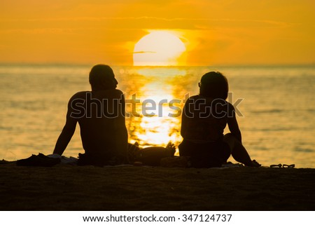 silhouette Happy Romantic Couple Enjoying Beautiful Sunset at the Beach - stock photo