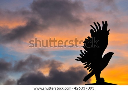 Silhouette hawk among sunset sky and color of light, famous attraction in Chumphorn, south Thailand - stock photo