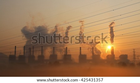 Silhouette high voltage transmission line and smoke from coal power plant background, Industry pollution in foggy day - stock photo