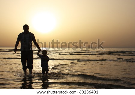Silhouette image of father and his child by the sea shore, sunset - stock photo