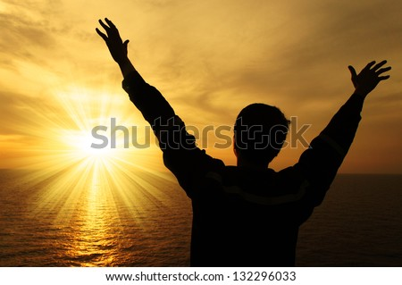Silhouette Image of Man Raising His Hands With Ray of Light - stock photo