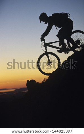 Silhouette image of mountain biker riding down slope - stock photo