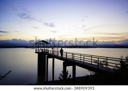 Silhouette image of sunset at reservoir with the man waiting:select focus with shallow depth of field:ideal use for background. - stock photo