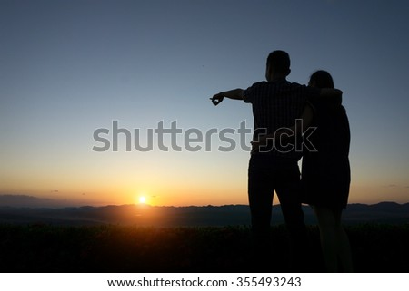 silhouette lovers Hands up against sunset time with lens flare - stock photo