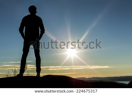 Silhouette male standing on a mountain top looking into the distance at sunset - stock photo