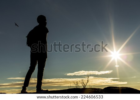 Silhouette male with a backpack on top of a mountain or hill looking into the distance as the sun begins to set - stock photo