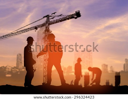 silhouette man construction worker in a building site over Blurred construction worker on construction site  - stock photo