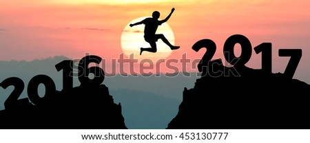 silhouette man jumps to make the word Happy New Year 2017 with sunrise. (New Year 2017 is coming concept.) - stock photo