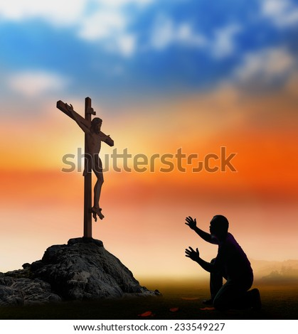 Silhouette man kneeling and raising hands to Jesus on the cross over blurred a sunset background. - stock photo
