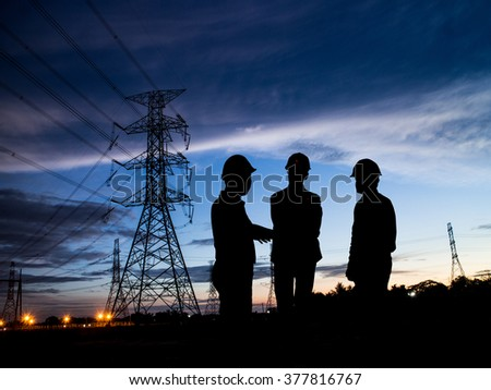 silhouette man of engineers standing at electricity station over Blurred electricity power - stock photo