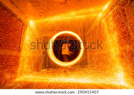 silhouette Man Spinning the Burning Steel Wool At Night,long exposure - stock photo