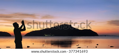 Silhouette man take Video, Twilight before sunrise at the beach, in Phuket, Thailand, Panorama Landscape. - stock photo