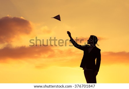 Silhouette man throwing paper plane - stock photo