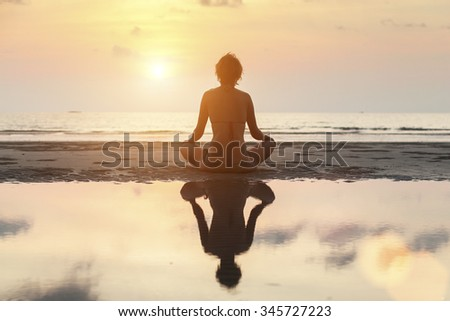 Silhouette meditation girl on the background of the stunning sea and sunset.  - stock photo