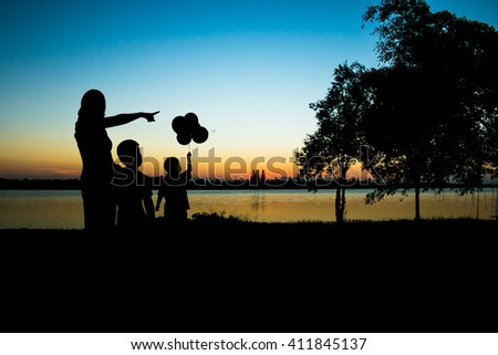 Silhouette Mother and son looking sunset  - stock photo
