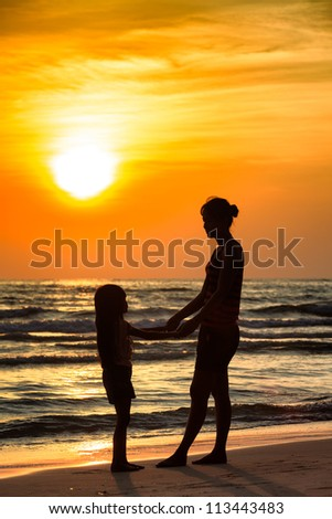 Silhouette mother with daughter ashore on sunset - stock photo