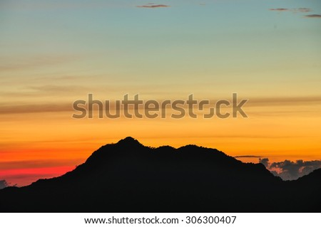 Silhouette mountain and space of sunset sky - stock photo