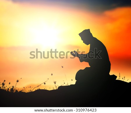Silhouette muslim man sitting and praying at golden autumn sunset background during the month of ramadan. Eid Mawlid An Nabi, Milad Un Nabi, Prophet's Birthday, Muhammad, Muhammed, Mohammad concept. - stock photo