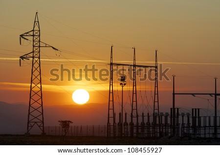silhouette of a alectrical substation and setting sun, La Muela, Zaragoza, Aragon, Spain - stock photo