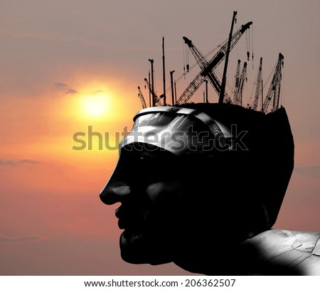 Silhouette of a android robot head with construction crane and machinery against a fiery skyscape, for the concept of reconstruction of mindset. - stock photo