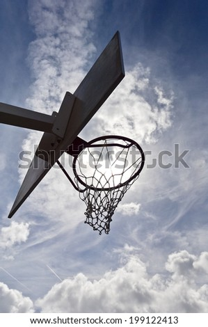 Silhouette of a basketball hoop against a cloudy sky. - stock photo