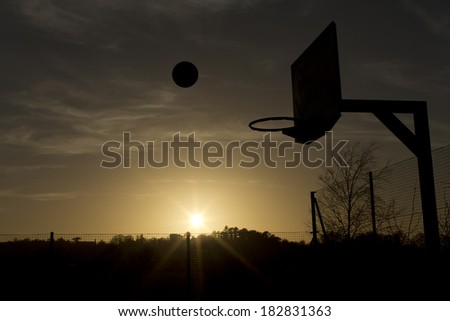 Silhouette of a basketball in mid air over the sunset about to score. Concept of sport, with copy space and sun flare - stock photo
