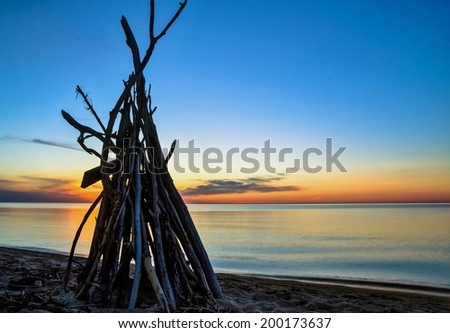 Silhouette of a beach hut with a sunset horizon as the backdrop .  - stock photo