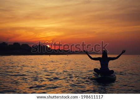 Silhouette of a beautiful girl engage paddle board yoga at the perfect orange sunset over the ocean, spiritual yoga meditation on the beach - stock photo