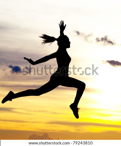 Silhouette of a beautiful jumping woman against yellow sky with clouds at sunset - stock photo