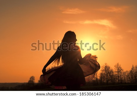 Silhouette of a beautiful young woman in a floaty dress  - stock photo