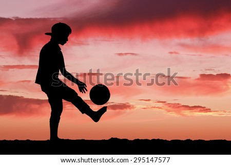 Silhouette of a boy playing football or soccer at the beach with beautiful sunset background Childhood, serenity, sport, lifestyle concept - stock photo