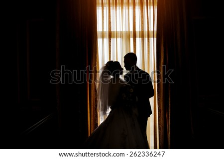 Silhouette of a bride and groom on the background of a window with curtains. - stock photo