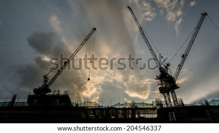 Silhouette of a building under Construction at sunset - stock photo