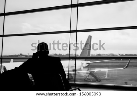 Silhouette of a businessman making a phone call in an airport gate - stock photo