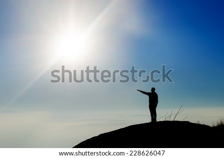 Silhouette of a champion on mountain top pointing toward sun. Sport and active life concept - stock photo