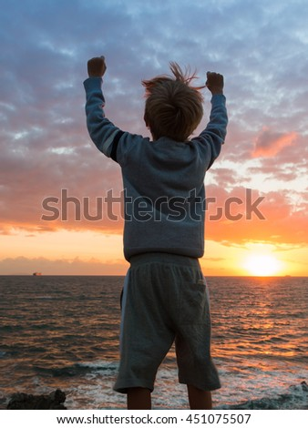 Silhouette of a Child in Front of Sea at Sunset: Winner Attitude - stock photo