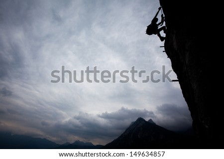 Silhouette of a climber above mountain peaks. Great copy space. - stock photo