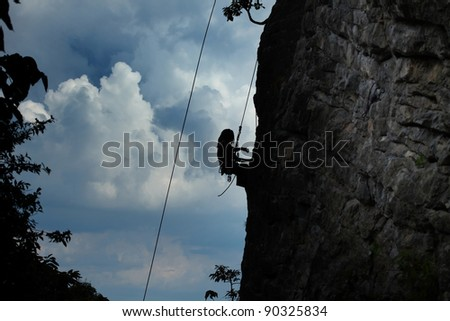 Silhouette of a climber hanging on a rope by cliff with blue stormy clouds on the background - stock photo