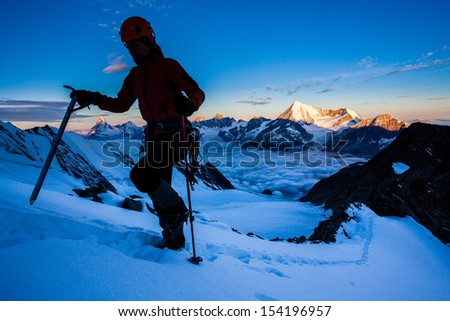 Silhouette of a climber on a glacier with high peaks in the background - stock photo
