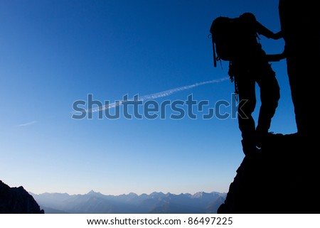 Silhouette of a climber with large copy space - stock photo