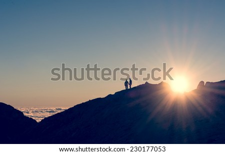 silhouette of a couple holding hands on a mountain ridge with sun rising - stock photo