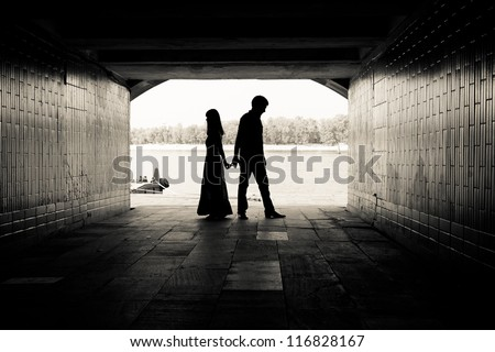 Silhouette of a couple on bright background at the end of an underground pedestrian tunnel - stock photo